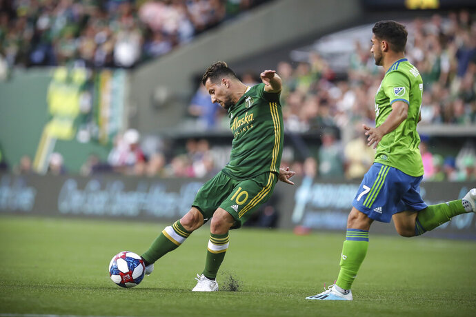 Portland Timbers' Sebastian Blanco strikes the ball next to Seattle Sounders' Cristian Roldan during the first half of an MLS soccer match Friday, Aug. 23, 2019, in Portland, Ore. (Serena Morones/The Canadian Press via AP)
