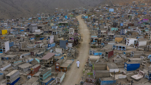Brother Ronald Marin, a 30-year-old layworker from Venezuela, walks along a paved dirt road lined by graves, inside the