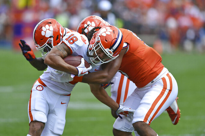 Clemson's T.J. Chase (18) is tackled by Shaq Smith, right, and Denzel Johnson, back, during Clemson's annual Orange and White NCAA college football spring scrimmage Saturday, April 6, 2019, in Clemson, S.C. (AP Photo/Richard Shiro)