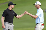 Harris English, right, greets Daniel Berger on the 18th green during the third round of the Tournament of Champions golf event, Saturday, Jan. 9, 2021, at Kapalua Plantation Course in Kapalua, Hawaii. (Matthew Thayer/The Maui News via AP)