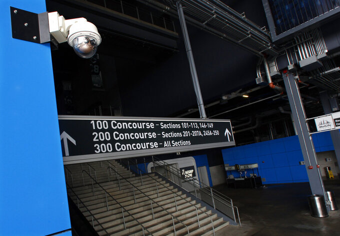 """FILE - In this Oct. 15, 2014, file photo, a security camera, upper left, is mounted near a stairway at MetLife Stadium, home of the New York Giants and the New York Jets football teams, in East Rutherford, N.J. Dave Karls has Bucks season tickets and is eager enough for his next visit to Fiserv Forum that having his location trackable in the arena would not interfere with the enjoyment. """"I'd much rather have that than not be able to attend the game at all,"""" Karls said. Such concern depends on an individual's definition of surveillance, a word that carries nefarious connotation in some corners.  (AP Photo/Mel Evans, File)"""