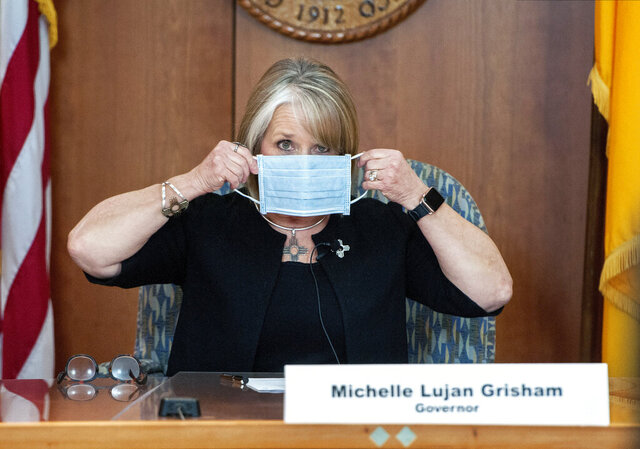 FILE - In this April 15, 2020, file photo, New Mexico Gov. Michelle Lujan Grisham puts on her face mask when not speaking during an update on the COVID-19 outbreak in the state during a news conference in the state Capitol in Santa Fe, N.M. Gov. Lujan Grisham used her line-item veto power to preserve executive control over hundreds of millions of dollars in federal coronavirus relief funding, a move that could mean the loss of additional financial assistance for some Native American communities. She used her veto pen to scratch out entire paragraphs of the budget to prevent the Legislature from earmarking $318 million in federal virus relief funding for local governments. (Eddie Moore/The Albuquerque Journal via AP, Pool, File)