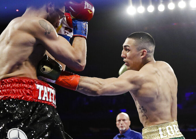 FILE - In this April 20, 2019, file photo, Teofimo Lopez, right, punches Finland's Edis Tatli during the first round of a boxing bout in New York. Lopez is symptomatic after testing positive for COVID-19, and his bout with mandatory challenger George Kambosos has been postponed until Aug. 14. Lopez and Kambosos were scheduled to fight Saturday night at the Miami Marlins' home stadium. (AP Photo/Frank Franklin II, File)