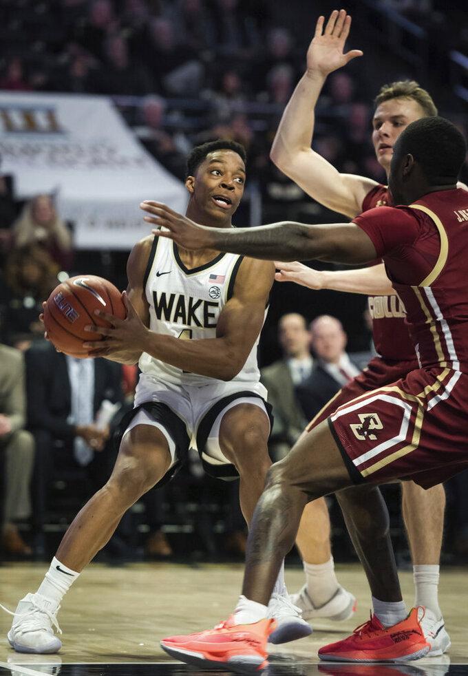 Wake Forest guard Jahcobi Neath (4) looks for an opening past Boston College forward Luka Kraljevic (13) and guard Jay Heath (5) in the first half of a college basketball game  Sunday, Jan. 19, 2020, in Winston-Salem, N.C. (Allison Lee Isley/Winston-Salem Journal via AP)