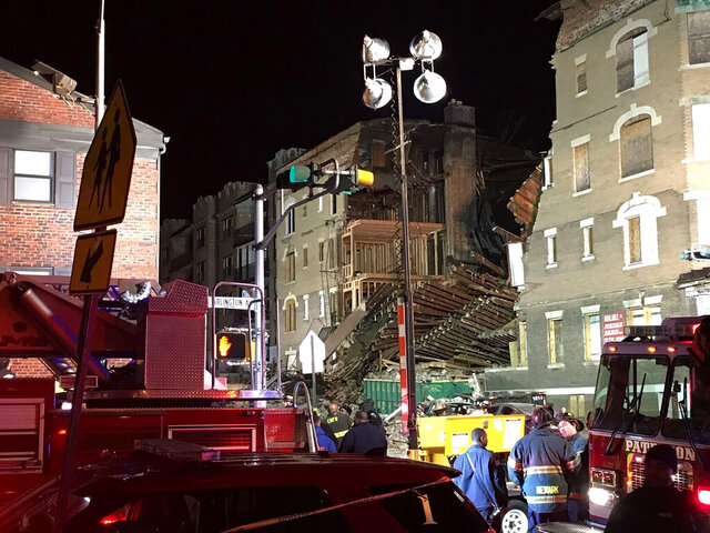 First responders work the scene after a building in East Orange, N.J., collapsed Saturday evening, Feb. 22, 2020. The building partially collapsed Saturday, spilling debris into the street. There was no word on any injuries at the time of this reporting, but authorities launched a search for anyone who might be in the rubble. (Blake Nelson/NJ Advance Media via AP)