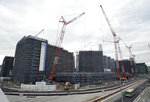 In this Feb. 12, 2019, photo, cranes continue to work at the construction site of the Olympic Village for the 2020 Tokyo Olympics in Tokyo. An IOC inspection team began a routine tour of venues being built for the Tokyo Olympics on Tuesday, May 21, 2019, just days after an international labor union federation derided difficult working conditions at some sites. (AP Photo/Eugene Hoshiko)