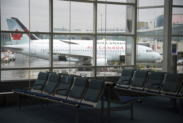 A plane is seen through the window on the tarmac of Vancouver International Airport as the waiting room is empty Tuesday, June 9, 2020. Airlines in Canada and around the world are suffering financially due to the lack of travel and travel bans due to COVID-19. (Jonathan Hayward/The Canadian Press via AP)