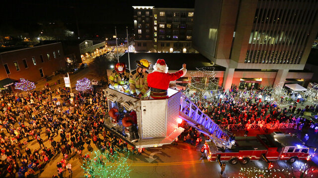 In this Dec. 4, 2015 photo, people gather at the intersection of Ninth and Massachusetts streets as Santa Claus is heroically rescued from the roof of Weaver's department store by two Lawrence firefighters in a ladder truck in Lawrence, Kan.  This event is not happening this year as the pandemic strains hospitals. Instead, Santa will appear on the first three Saturdays of December atop a truck decked out in garlands, poinsettias and pine cones.   (The Lawrence Journal-World via AP)