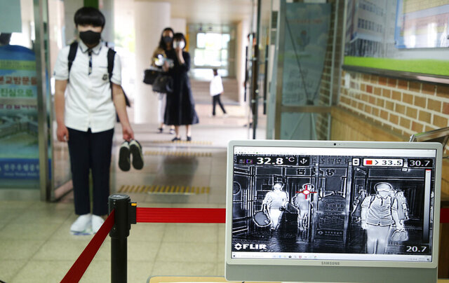 A student wearing a face mask to help protect against the spread of the new coronavirus stands to have his body temperatures checked before entering his classroom at a middle school in Jeonju, South Korea, Wednesday, Jun 3, 2020. (Na Bo-bae/Yonhap via AP)