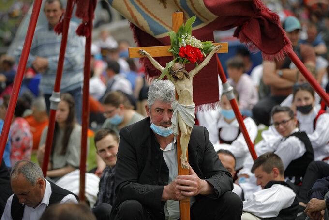 A man holds a crucifix as Catholic pilgrims fill the hillsides after tens of thousands joined their faith's biggest religious event in Sumuleu Ciuc, Romania, Saturday, May 22, 2021. More than 35,000 Catholic pilgrims congregated at an open-air shrine in Sumuleu Ciuc in Transylvania on Saturday for an age-old procession that last year was canceled due to the coronavirus pandemic. (AP Photo/Vadim Ghirda)