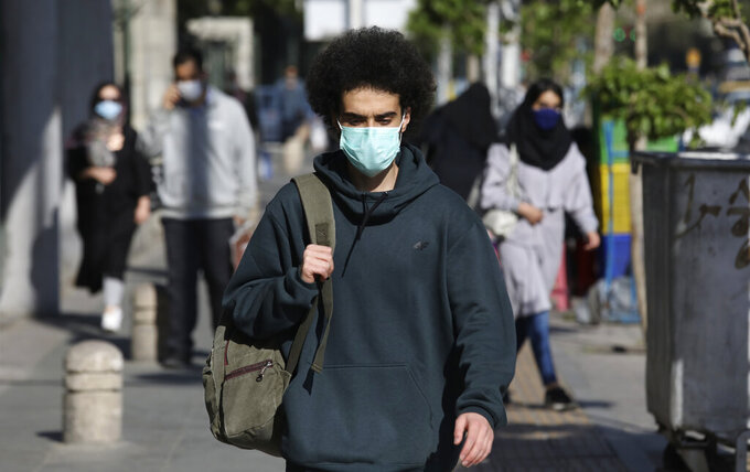 People wearing protective face masks to help prevent the spread of the coronavirus walk on a sidewalk in downtown Tehran, Iran, Monday, April 5, 2021. Iran shattered its daily record for new coronavirus infections Wednesday for the second consecutive day, with recorded cases soaring to 20,954. (AP Photo/Vahid Salemi)