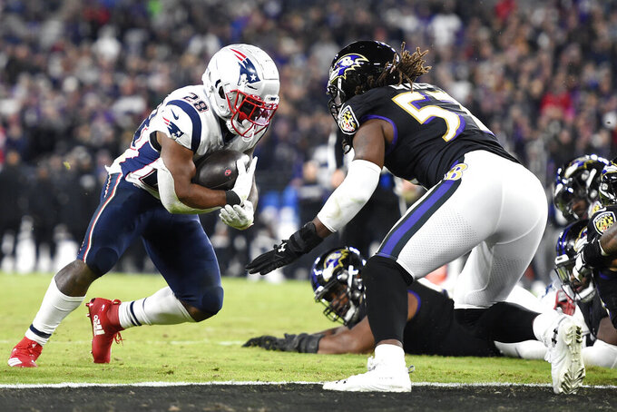 New England Patriots running back James White, left, scores on a touchdown run as Baltimore Ravens linebacker Josh Bynes (57) tries to stop him during the second half of an NFL football game, Sunday, Nov. 3, 2019, in Baltimore. (AP Photo/Gail Burton)