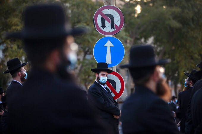Ultra-Orthodox Jews wear face masks and keep social distancing amid concerns over the country's coronavirus outbreak, during a protest to what they say is incitement against the city and country's religious population in the southern Israel city of Arad, Israel, Monday, Oct. 19, 2020. (AP Photo/Oded Balilty)