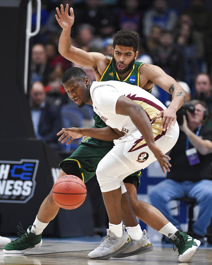 Vermont's Anthony Lamb, back, guards Florida State's Raiquan Gray during the first half of a first round men's college basketball game in the NCAA tournament, Thursday, March 21, 2019, in Hartford, Conn. (AP Photo/Jessica Hill)