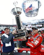 Food City president and CEO, Steve Smith, left, holds the trophy with race winner Kyle Busch after a NASCAR Cup Series auto race, Monday, April 16, 2018 in Bristol, Tenn. (AP Photo/Wade Payne)