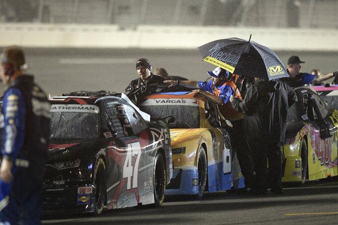 Crew members cover cars on pit road during a rain delay at a NASCAR Xfinity Series auto race at Daytona International Speedway, Friday, Aug. 27, 2021, in Daytona Beach, Fla. (AP Photo/Phelan M. Ebenhack)