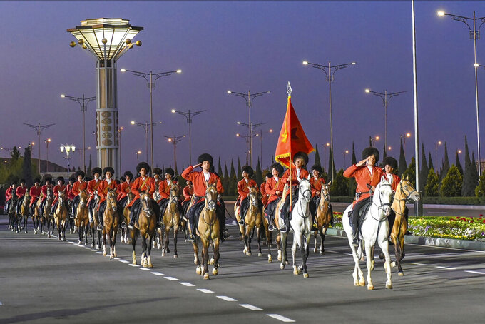 FIE - In this May 9, 2020, photo, Turkmenistan's soldiers dressed in national uniforms ride their horses during the celebration of the 75th anniversary of the Nazi defeat in World War II in Ashgabat, Turkmenistan. As with North Korea, there is significant doubt about Turkmenistan's claim of zero cases. Authorities in the secretive and authoritarian Central Asian nation of 6 million have rejected allegations they're hiding information about the outbreak. And yet health officials have recommended people wear masks and keep a distance of 2 meters (7 feet) from each other in public places. (AP Photo,File)