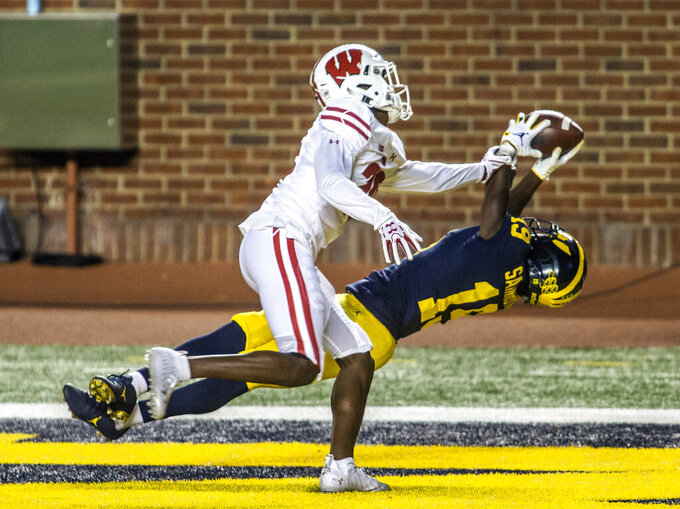 Michigan wide receiver Mike Sainristil (19) makes a touchdown catch while defended by Wisconsin cornerback Semar Melvin (20) in the third quarter of an NCAA college football game in Ann Arbor, Mich., Saturday, Nov. 14, 2020. (AP Photo/Tony Ding)