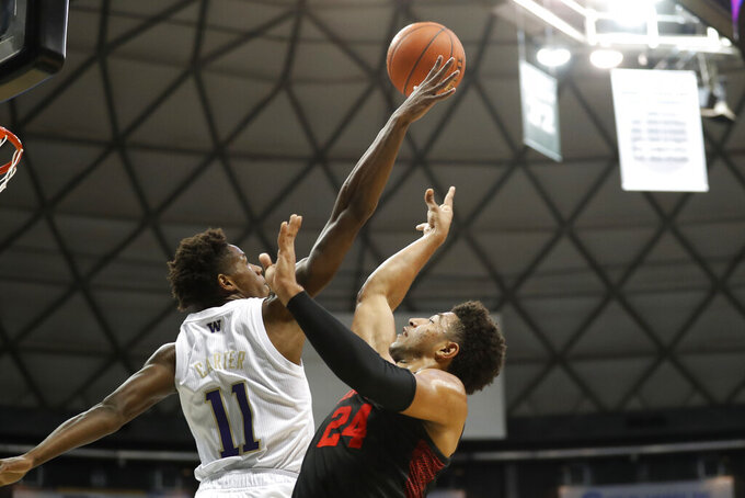 Houston guard Quentin Grimes (24) shoots over Washington guard Nahziah Carter (11) during the first half of an NCAA college basketball game Wednesday, Dec. 25, 2019, in Honolulu. (AP Photo/Marco Garcia)