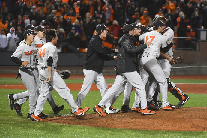 Oregon State players rush the mound after their victory over Minnesota during an NCAA college baseball tournament super regional game Saturday, June 9, in Corvallis, Ore. (Amanda Loman/Albany Democrat-Herald via AP)