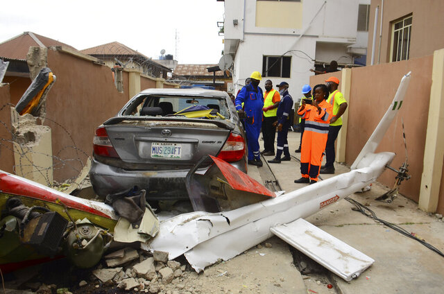 People gather at the site of a helicopter crash in Lagos, Nigeria Friday, Aug. 28, 2020. Authorities say two people have died and a third is critically injured after a helicopter crashed into a residential area in Nigeria's most populous city, Lagos. The National Emergency Management Agency says the dead include the pilot and a passenger in the helicopter operated by Quorum Aviation. The third person was also in the helicopter. (AP Photo)