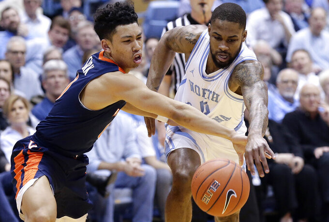 Virginia's Kihei Clark, left, and North Carolina's Seventh Woods, right, reach for the ball during the first half of an NCAA college basketball game in Chapel Hill, N.C., Monday, Feb. 11, 2019. (AP Photo/Gerry Broome)