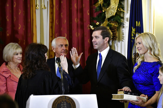 Kentucky Supreme Court Justice Michelle M. Keller, foreground left, gives the oath of office to Andy Beshear to become the state's governor in Frankfort, Ky., early Tuesday, Dec. 10, 2019. Holding the Bible is Beshear's wife, Britainy (AP Photo/Timothy D. Easley, Pool)