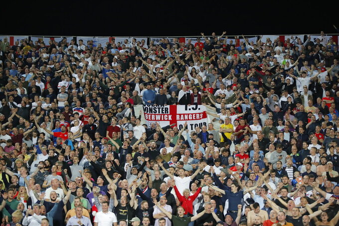 FILE - In this Monday, Oct. 14, 2019 file photo, England fans celebrate during the Euro 2020 group A qualifying soccer match between Bulgaria and England, at the Vasil Levski national stadium, in Sofia, Bulgaria. UEFA set itself a challenge deciding nine years ago to let a dozen cities around Europe host its marquee European Championship in 2020. The multi-country project means more fans can see their own team in a stadium than if Euro 2020 was being traditionally hosted by a single nation amid international travel restrictions. (AP Photo/Vadim Ghirda, File)