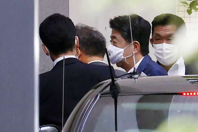 Japanese Prime Minister Shinzo Abe, center right, arrives at Keio University Hospital in Tokyo Monday, Aug. 24, 2020. Prime Minister Abe on Monday became Japan's longest-serving leader in terms of consecutive days in office, but there was little fanfare, as he visited a hospital for another health checkup amid concerns about his health.(Kyodo News via AP)