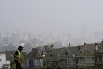 A worker waters grass at Alamo Square Park as smoke from wildfires and fog obscures the skyline above the