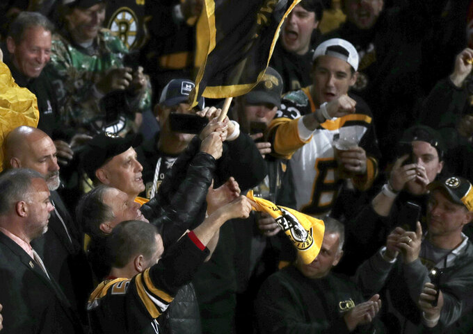 New England Patriots head coach Bill Belichick, lower left, waves the Boston Bruins banner before Game 2 of the NHL hockey Stanley Cup Final between Bruins and the St. Louis Blues, Wednesday, May 29, 2019, in Boston. (AP Photo/Charles Krupa)