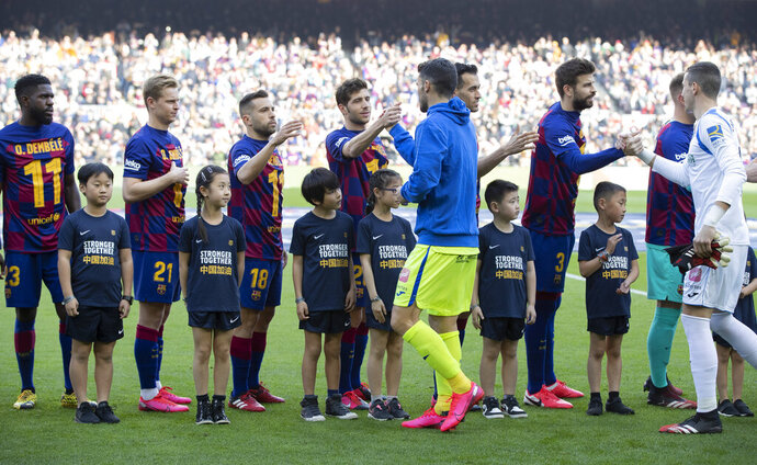 Barcelona players wearing Ousmane Dembele shirts in support of their seriously injured team mate shake hands with Getafe players in the company of boys and girls of Chinese origin from the Penya Dracs Units Xinesos, the Chinese FC Barcalona supporters club based in Barcelona, wearing a shirt with the message Stronger Together in English and