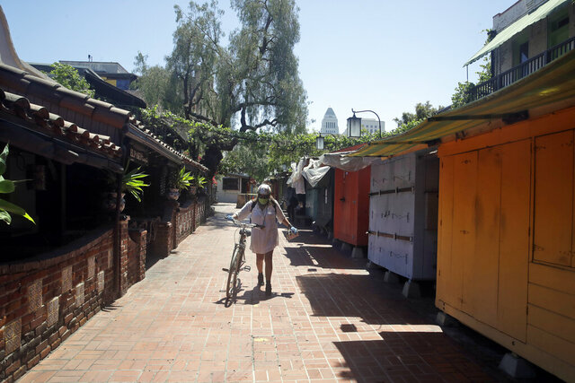 Christine Olivarri walks along the shuttered shops on Olvera Street amid the COVID-19 pandemic Tuesday, May 5, 2020, in Los Angeles. (AP Photo/Marcio Jose Sanchez)