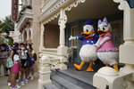 Visitors wearing face masks line up to take selfie with the iconic cartoon characters Donald Duck and Daisy Duck at the Hong Kong Disneyland, Friday, Sept. 25, 2020. Hong Kong Disneyland reopened its doors to visitors after closed temporarily due to the coronavirus outbreak. (AP Photo/Kin Cheung)