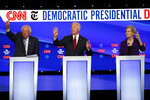 Democratic presidential candidate Sen. Bernie Sanders, I-Vt., left, former Vice President Joe Biden, center, and Sen. Elizabeth Warren, D-Mass., raise their hands to speak during a Democratic presidential primary debate hosted by CNN/New York Times at Otterbein University, Tuesday, Oct. 15, 2019, in Westerville, Ohio. (AP Photo/John Minchillo)