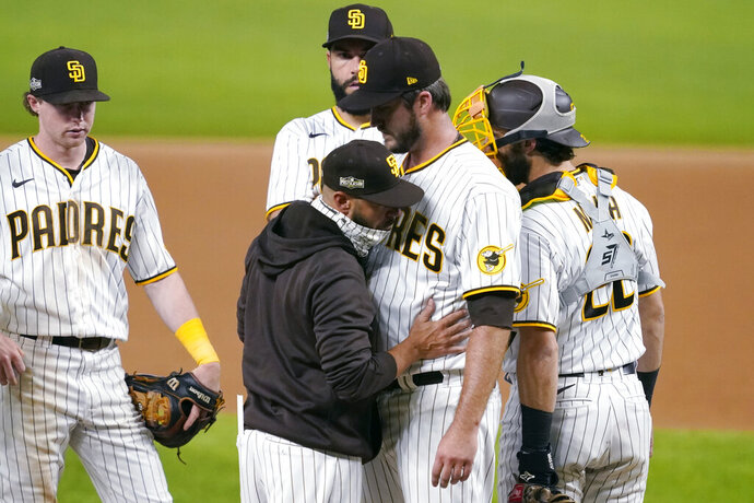 San Diego Padres manager Jayce Tingler, in jacket, takes pitcher Drew Pomeranz out of the game against the Los Angeles Dodgers during the eighth inning in Game 3 of a baseball National League Division Series Thursday, Oct. 8, 2020, in Arlington, Texas. (AP Photo/Tony Gutierrez)