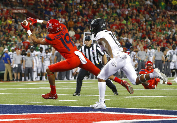 Arizona wide receiver Shawn Poindexter (19) makes the catch for a touchdown in front of Oregon cornerback Deommodore Lenoir in the second half during an NCAA college football game, Saturday, Oct. 27, 2018, in Tucson, Ariz. (AP Photo/Rick Scuteri)
