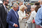 Britain's Prince Charles, second left, and his wife Camilla, center, greet members of the public during a walk at Viaduct Harbour in Auckland during their royal visit to New Zealand, Tuesday, Nov. 19, 2019. The visit is part of a week-long tour of the country which also takes in Christchurch and Kaikoura. (David Rowland/Pool Photo via AP)