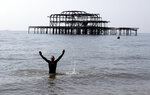 People take a swim in the sea on a warm and sunny day after the coronavirus outbreak and lockdown in Brighton, England, Saturday, April 11, 2020. in London, Saturday, April 11, 2020. The new coronavirus causes mild or moderate symptoms for most people, but for some, especially older adults and people with existing health problems, it can cause more severe illness or death.(AP Photo/Frank Augstein)