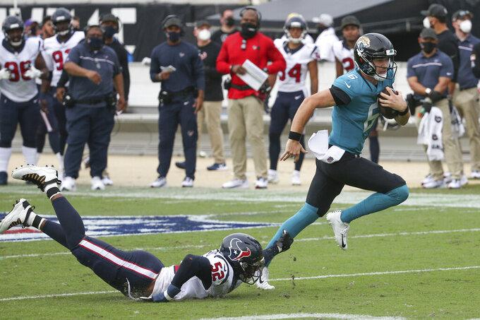 Jacksonville Jaguars quarterback Jake Luton, right, escapes a tackle by Houston Texans linebacker Jonathan Greenard (52) during the second half of an NFL football game, Sunday, Nov. 8, 2020, in Jacksonville, Fla. (AP Photo/Stephen B. Morton)