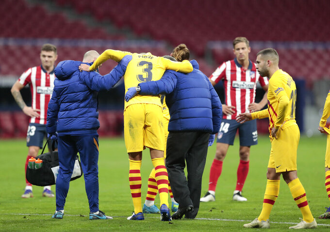 Barcelona's Gerard Pique is assisted from the pitch after getting an injury during the Spanish La Liga soccer match between Atletico Madrid and FC Barcelona at the Wanda Metropolitano stadium in Madrid, Spain, Saturday, Nov. 21, 2020. (AP Photo/Bernat Armangue)