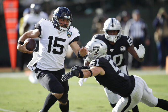 Jacksonville Jaguars quarterback Gardner Minshew runs with the ball away from Oakland Raiders inside linebacker Will Compton (51) and linebacker Nicholas Morrow (50) during the first half of an NFL football game in Oakland, Calif., Sunday, Dec. 15, 2019. (AP Photo/Ben Margot)