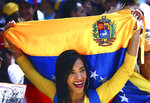 A woman, holding a Venezuelan national flag, smiles as she listens to opposition leader and self-proclaimed interim president Juan Guaido during a demonstration against the government of President Nicolas Maduro, in Caracas, Venezuela, Tuesday, Feb. 12, 2019. Venezuela's opposition has called its supporters into the streets across the country in a campaign to break the military's support of Maduro, who refuses to let emergency food and medicine from the United States across the border.(AP Photo/Boris Vergara)