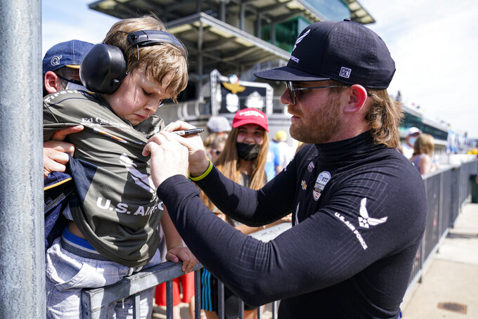 Conor Daly signs the shirt of a young fan during practice for the Indianapolis 500 auto race at Indianapolis Motor Speedway in Indianapolis, Friday, May 21, 2021. (AP Photo/Michael Conroy)