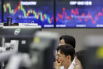 A currency trader watches computer monitors near the screens showing the foreign exchange rates at the foreign exchange dealing room in Seoul, South Korea, Wednesday, June 19, 2019. Asian shares were mostly higher Wednesday on optimism about trade after President Donald Trump said he will talk with the Chinese leader later this month in Japan.(AP Photo/Lee Jin-man)