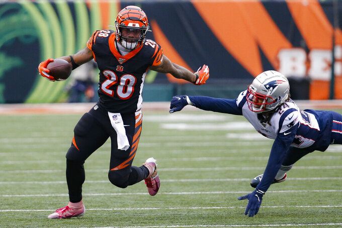 Cincinnati Bengals running back Joe Mixon (28) breaks a tackle by New England Patriots cornerback Stephon Gilmore (24) in the second half of an NFL football game, Sunday, Dec. 15, 2019, in Cincinnati. (AP Photo/Frank Victores)