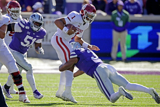 Oklahoma quarterback Jalen Hurts (1) is tackled by Kansas State linebacker Elijah Sullivan (3) during the second half of an NCAA college football game Saturday, Oct. 26, 2019, in Manhattan, Kan. Kansas State won 48-41. (AP Photo/Charlie Riedel)