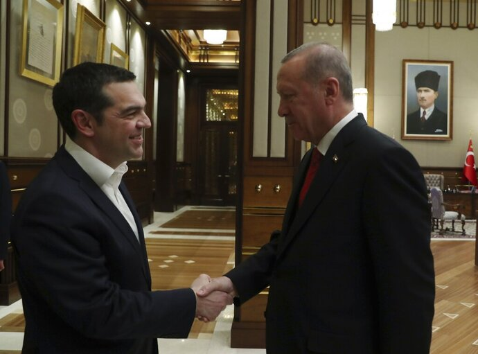 Turkey's President Recep Tayyip Erdogan, right, shakes hands with Greece's Prime Minister Alexis Tsipras during their meeting in Ankara, Tuesday, Feb. 5, 2019. A two-day visit by Greek Prime Minister Alexis Tsipras to Turkey got off to a shaky start Tuesday after Turkey put up bounties for the capture of eight Turkish servicemen who fled to Greece following a failed coup in 2016. (Presidential Press Service via AP, Pool)