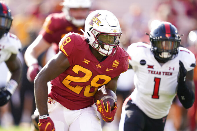 FILE - In this Oct. 10, 2020, file photo, Iowa State running back Breece Hall carries as Texas Tech linebacker Krishon Merriweather (1) pursues during the first half of an NCAA college football game in Ames, Iowa. Hall, the Big 12's leading rusher at 150.2 yards per game, has had at least 100 yards and a touchdown in every game this season. (AP Photo/Charlie Neibergall, File)