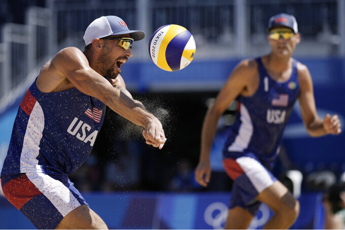 Nicholas Lucena, left, of the United States, returns a shot as teammate Philip Dalhausser watches during a men's beach volleyball match against Qatar at the 2020 Summer Olympics, Sunday, Aug. 1, 2021, in Tokyo, Japan. (AP Photo/Felipe Dana)